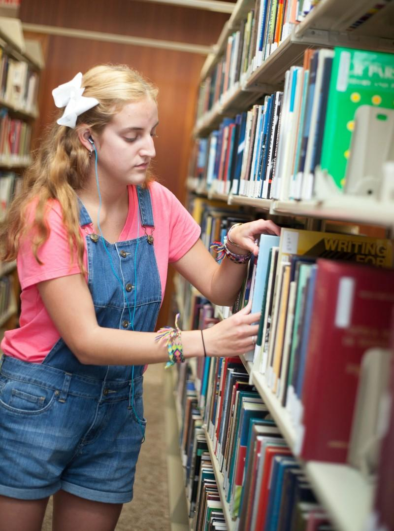 Josie Hammons, sophomore, spends her Tuesday evening organizing and shelving books at the library as a part time job. Photo by Anh-Viet Dinh.
