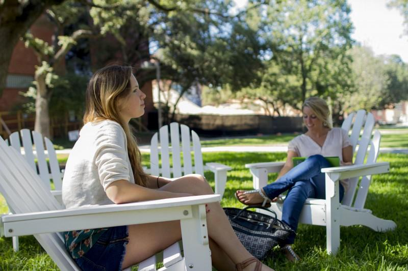 Seniors Frances Marshall and Leslie Butts enjoy the temperate weather while lounging between classes in the white lawn chairs provided by the urban studies department. Chairs can be found  next to Miller Fountain. Photo by Aidan Kirksey.