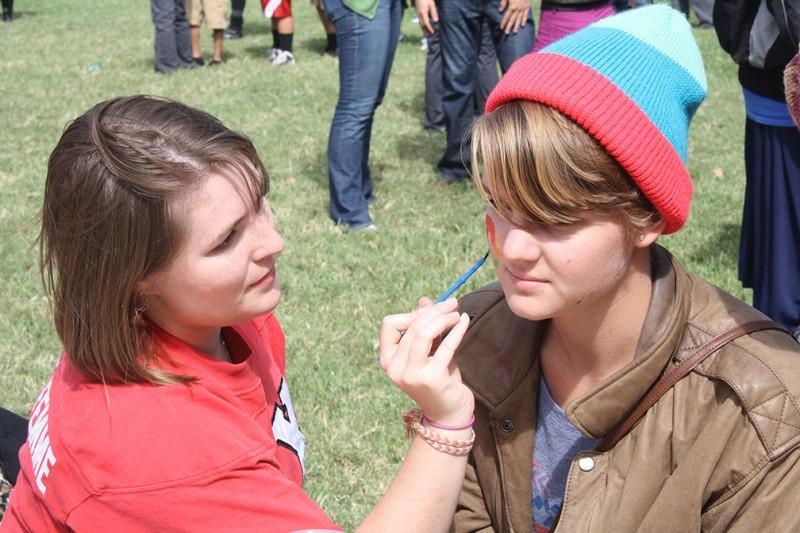 Junior Savannah McDonough paints a rainbow peace sign on sophomore Sarah Longridge's face during Big Six Carnival.