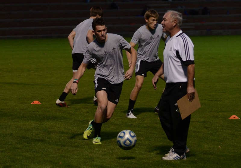 Junior Midfielder Alex Saadi dribbles the ball around head coach Paul McGinlay during spring training. Photo by Aidan Kirksey.
