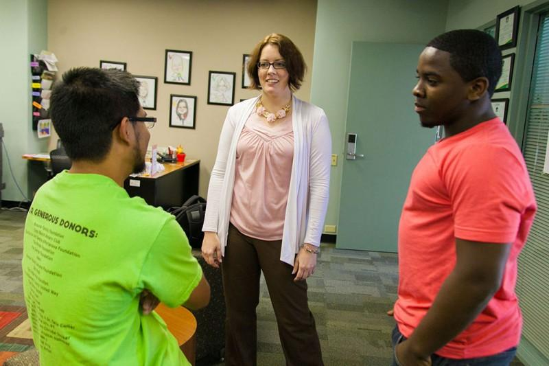 Junior Lawrence Pasaoa and sophomore chris Williams interact with Kate Polivka, the newly hired assistant director of Campus and Community Involvement, during 'milk and cookies' hour on Thursday. Photo by Anh-Viet Dinh.