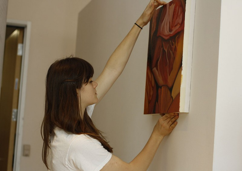 Senior Jennifer Lewish hangs a painting in preparation for the opening of