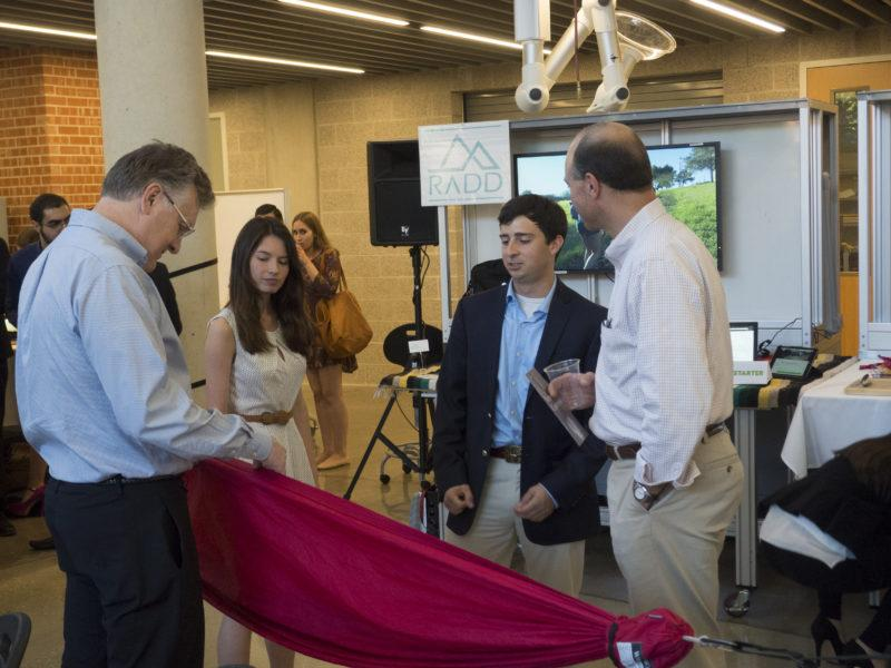 Photo by Henry Pratt.  Sarah Forin and Jamie Procter discuss the details of the lightweight, portable hammock as they promote their business, RADD, with guests at the Stumberg Competition.