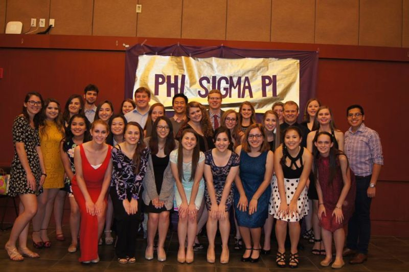 Members of Phi Sigma Pi pose for a photo at their 2016 Spring Banquet, where they celebrated receiving the Most Improved New Chapter Award with food, a photobooth and big and little reveal.