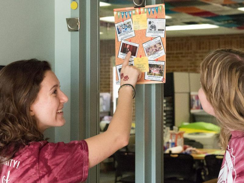 O-Team members COURTNEY JUSTUS and ELIZABETH BROUSSARD look at the Welcome Week calendar. photo by Amani Canada