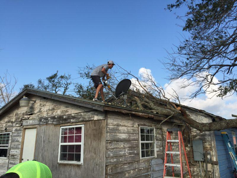 Senior tennis player Austin Crist helps clear debris from the roof of a damaged home in Aransas Pass. Photo provided by Russell McMindes