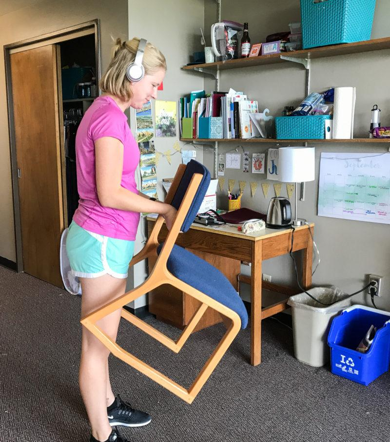 Julia Weis does a chair curl in her dorm room to work out her upper body. photo provided by Julia Weis