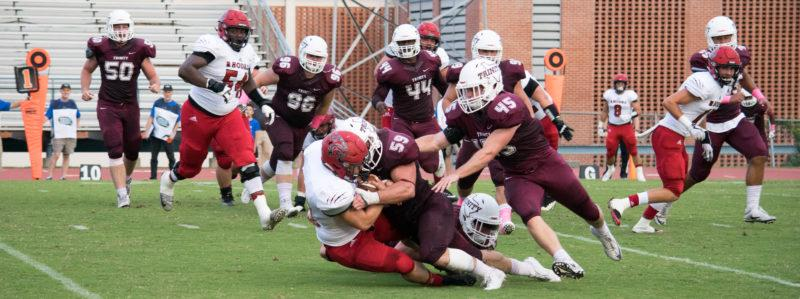 Senior linebacker Mitchell Globe tackles a Rhodes player to the ground. This win marks a streak for Tiger football in the SAA conference. photo by Allison Wolff