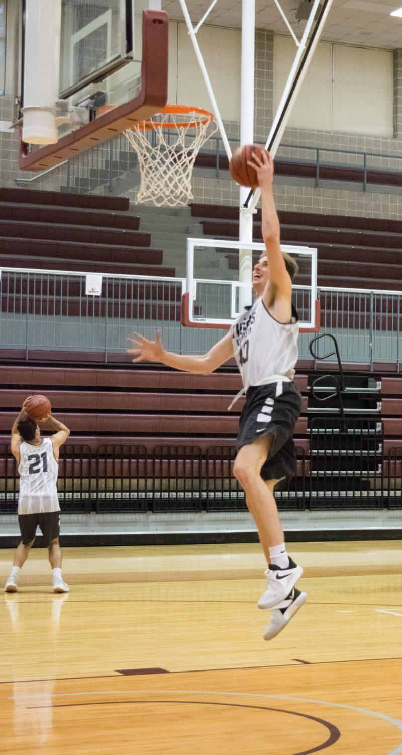 Senior Brian Blum reaches for the basket to make a shot at practice. Photo by Allison Wolff