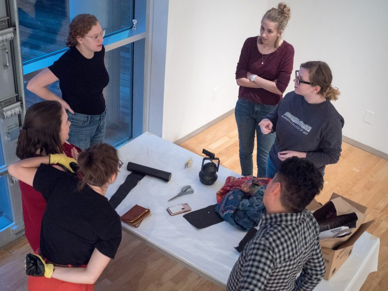 Students ARIEL DEL VECCHIO, ABIGAIL WHARTON, JULIA POAGE, KRISTINA REINIS, ELIZABETH DAY, and gallery manager MARK ANTHONY MARTINEZ prepare the exhibit before the next day's gallery opening. Photo by Amani Canada, photo editor