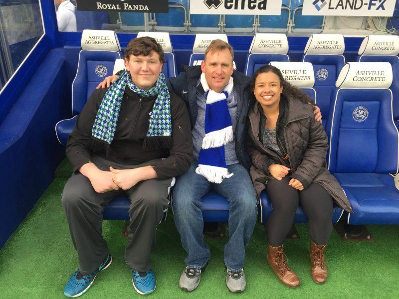 David Spindel, Jacob K. Tingle, and Hailey Wilson pose and smile while sitting at Loftus Street, the home stadium of the Queens Park Rangers. photo provided by Jacob K. Tingle