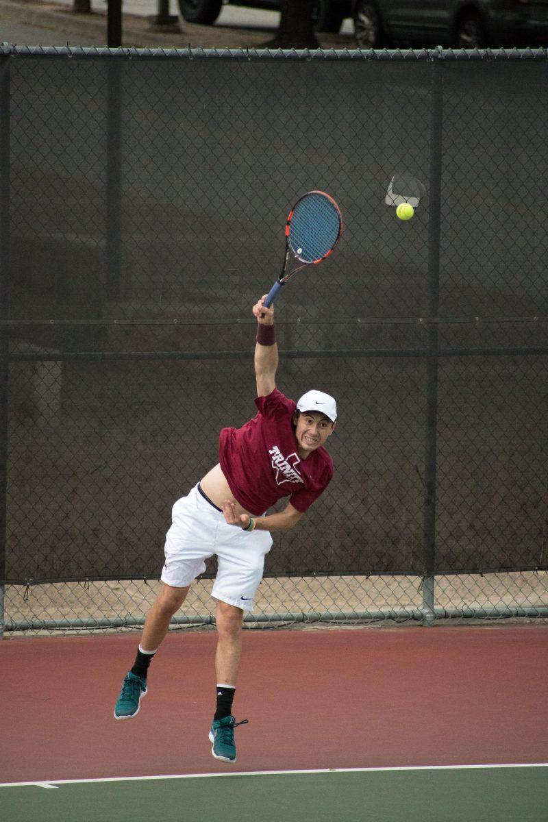 Junior Tilden Oliver serves in a match versus St. Edwards University  on Friday, Feb. 16. photo by Allison Wolff, staff photographer.