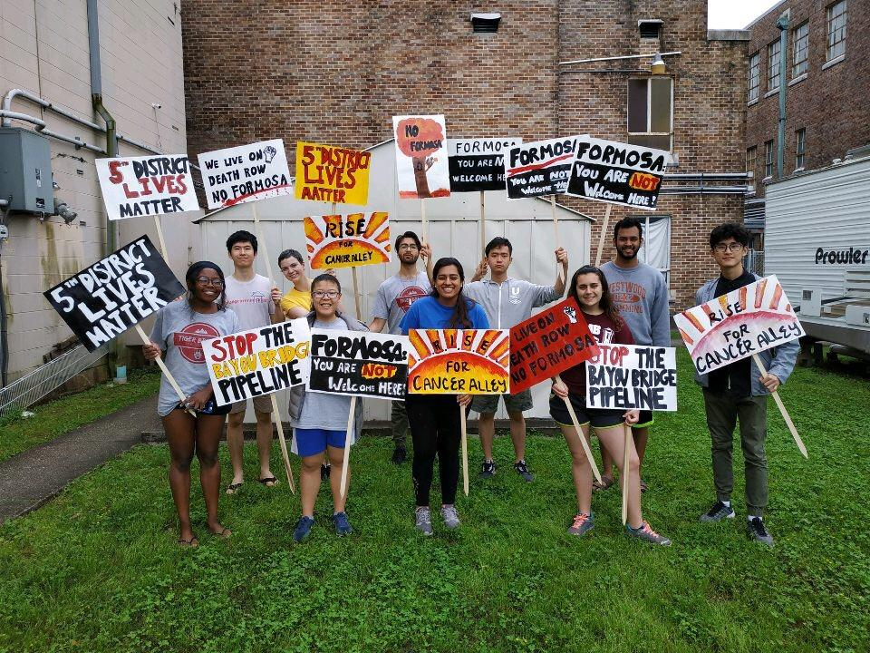 Students pose with signs they made to protest the building of a chemical plant in a low-income neighborhood. Photo provided by Danyal Tahseen