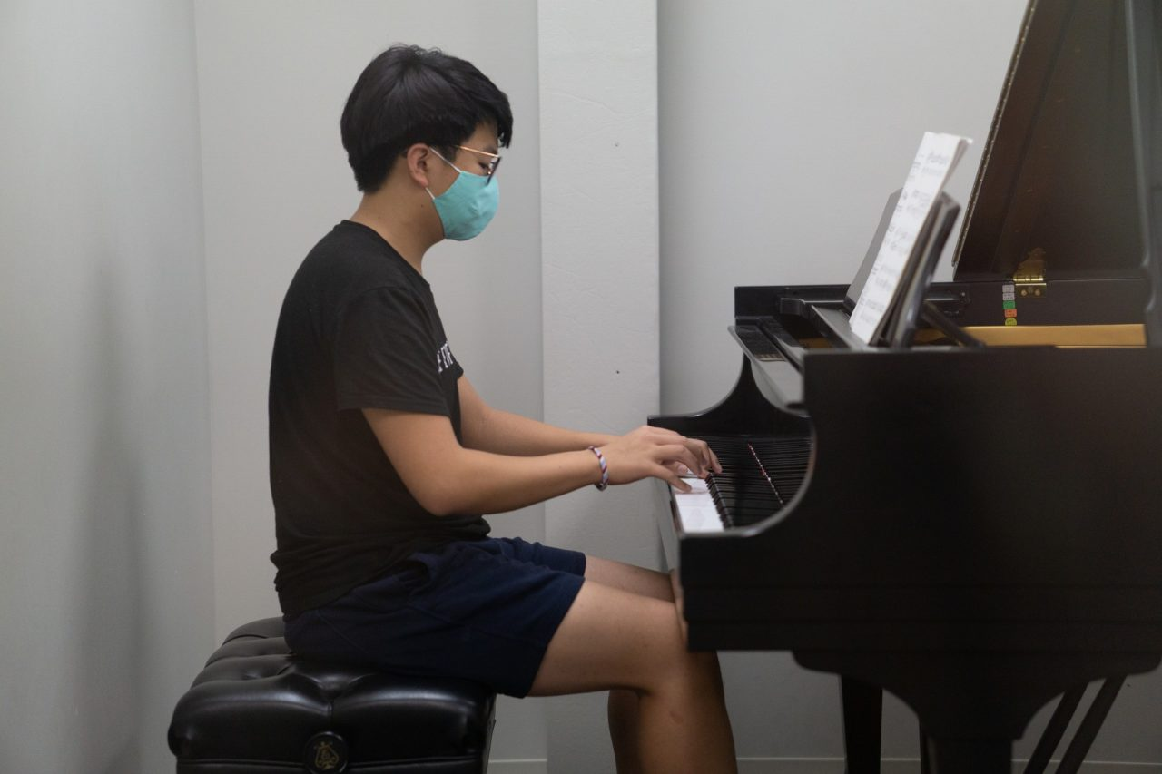 Student Jimmy Phan practices for his piano class with Dr. Carolyn True on campus. Students are a assigned a specific practice room, and must use a weekly sign up form to indicate their reservations. Additionally, students are responsible for wiping down pianos after use, and allowing the room to air out for fifteen minutes when they have finished practicing. Photo credit: Kate Nuelle