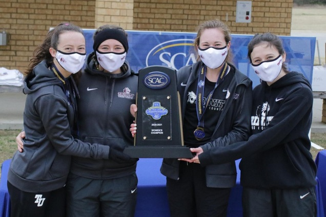 Members of the women's cross country team hold the SCAC Championship trophy. This was the Tigers' fifth SCAC team title.